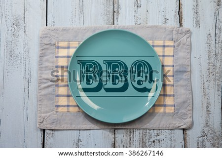 Empty plate with BBQ icon on light blue wooden background - stock photo