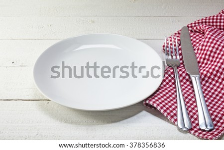 empty plate with cutlery and red white napkin on a white rustic wooden table, invitation to lunch or dinner
