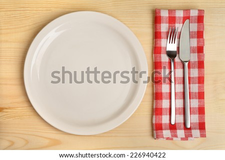 Empty plate with cutlery on red checkered napkin on wooden background. - stock photo