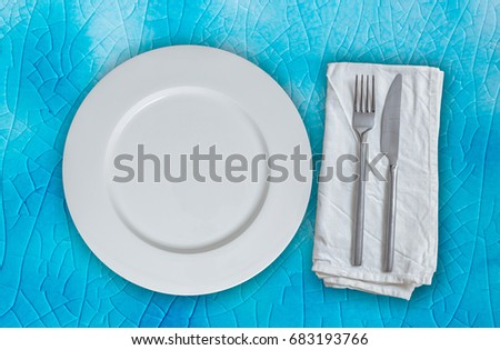 Empty plate with cutlery on turquoise background.