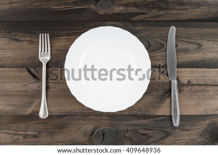 empty plate with fork and butter knife on wooden background