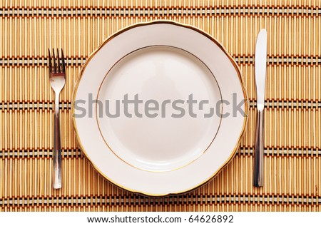empty plate with fork knife on table - stock photo