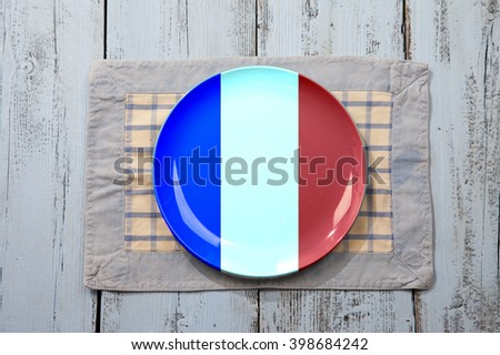Empty plate with French flag on light blue wooden background - stock photo