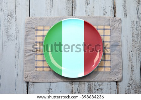 Empty plate with Italian flag on light blue wooden background - stock photo