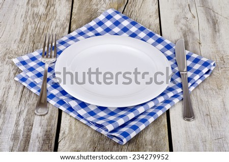 Empty plate with knife and fork  on blue-white checkered tablecloth on wooden table  - stock photo