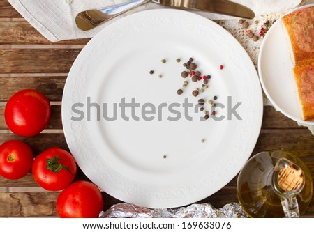 empty plate with tomatoes and olive oil waiting for food - stock photo