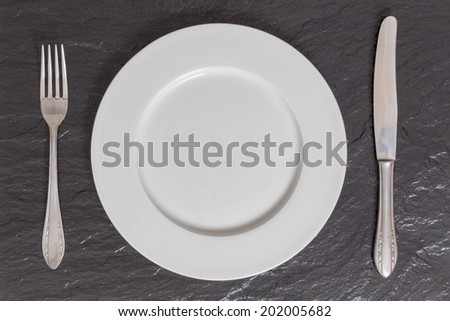 Empty plate with utensils on slate in bird's eye view.