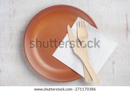 Empty plate with wooden fork and table knife on old table, top view - stock photo