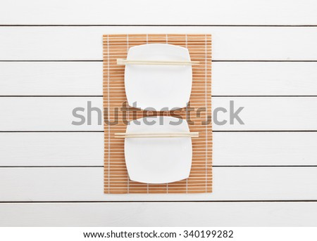Empty plates and chopsticks on white wooden background. Top view with copy space - stock photo