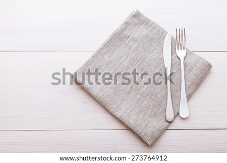 Empty plates and cutlery on table cloth on wooden table for dinner. Top view horizontally.