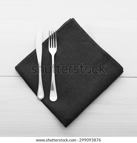 Empty plates and cutlery on table cloth on wooden table for dinner. Top view square.  Black and white photo.