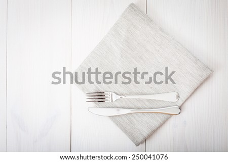Empty plates and cutlery on the table cloth on a wooden table for dinner. Top view horizontally. - stock photo
