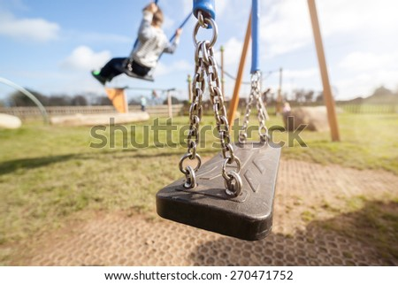 Empty playground swing with children playing in the background concept for child protection, abduction or loneliness - stock photo
