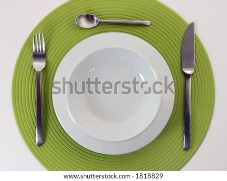 Empty porcelain plate with knife, fork and teaspoon on a green stylish cloth - stock photo