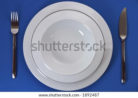 Empty porcelain plates, knife and fork - stock photo