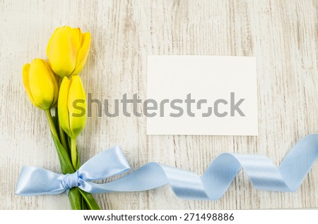 Empty postcard with colorful flowers and blue ribbon on wooden background - stock photo