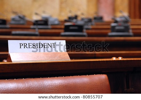 empty president seat in conference hall president conference place card in the empty conference room - stock photo