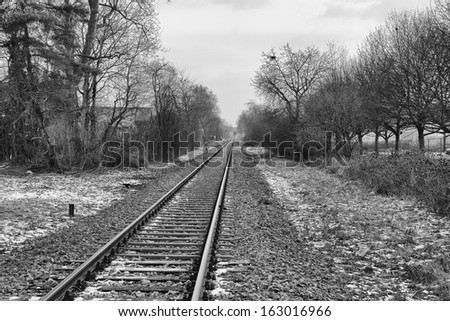 Empty railroad track leading into the hazy distance on a winter evening, monochromatic version