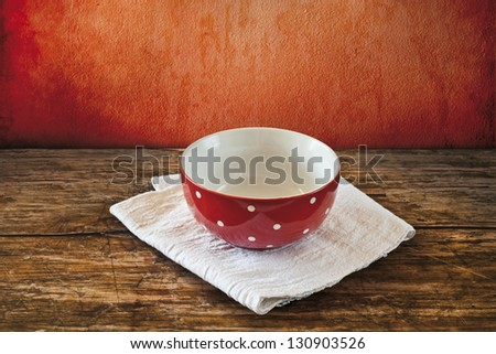 empty red bowl with white dots on a table - stock photo