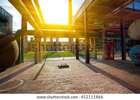 Empty red brick road surface floor with old abandoned closed steel steelworks of pipelines - stock photo