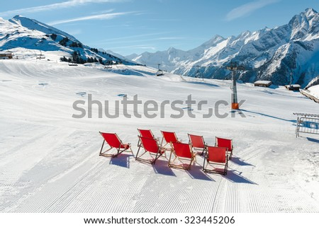 Empty red deck chairs on the snow in Mayrhofen ski resort, Austrian Alps - stock photo