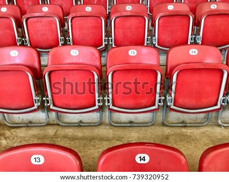 Empty red plastic seats in a stadium