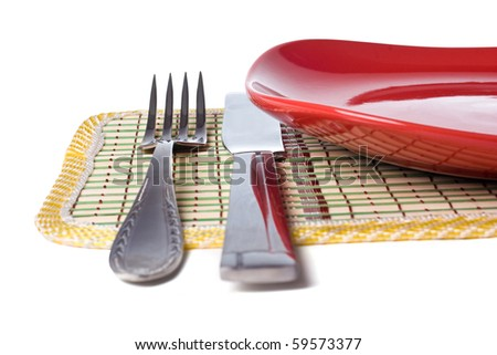Empty red plate with knife and fork - stock photo