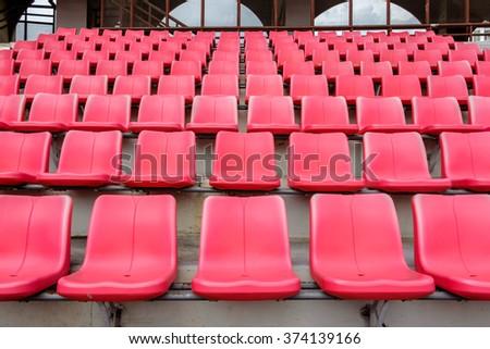 Empty red seats in football stadium. - stock photo