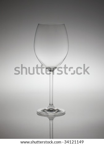 Empty red wine glass in back light. - stock photo