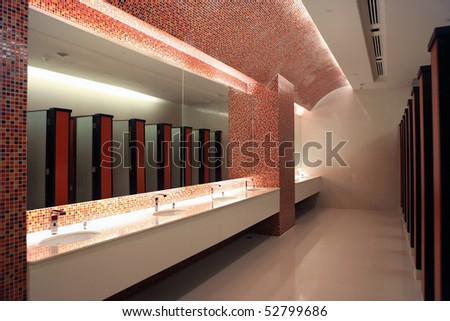 Empty restroom interior with washstands and toillets in mirror - stock photo