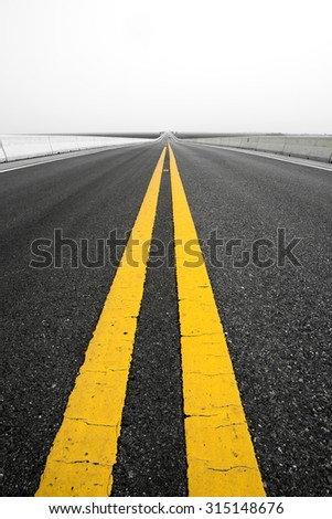 Empty road and old yellow traffic lines