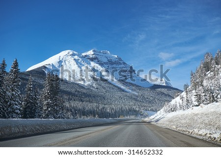 empty road at Banff Canada in winter, with snowy mountains and trees in the background - stock photo