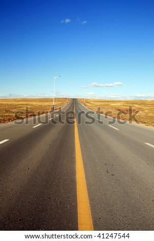 empty road in meadow with blue sky