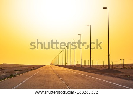 Empty road in the desert at sunset, United Arab Emirates - stock photo
