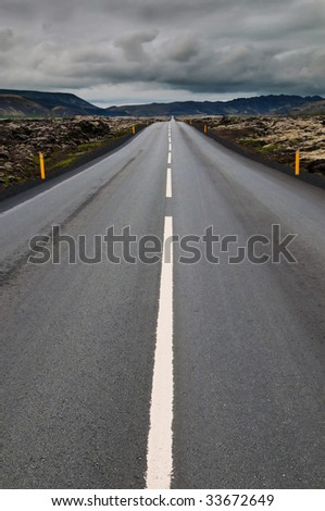 empty road leading to cloudy landscape - stock photo