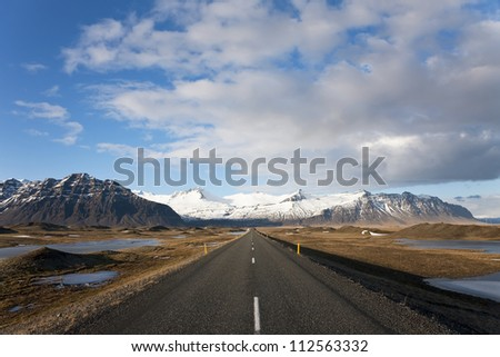 Empty road leading to snow covered mountains, Iceland - stock photo