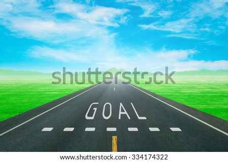 empty road through the green field with sign goal on asphalt - stock photo