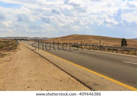 Empty road under sky in desert - stock photo