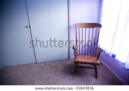 Empty rocking chair in room next to window - stock photo
