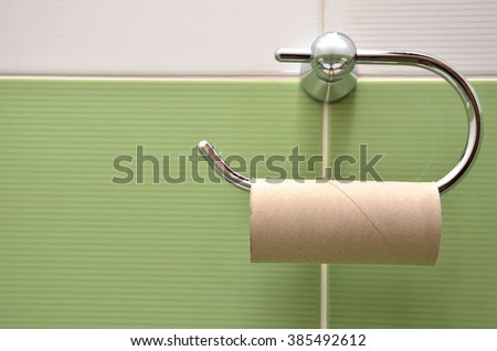 Empty roll on toilet paper holder with green white wall in background - stock photo