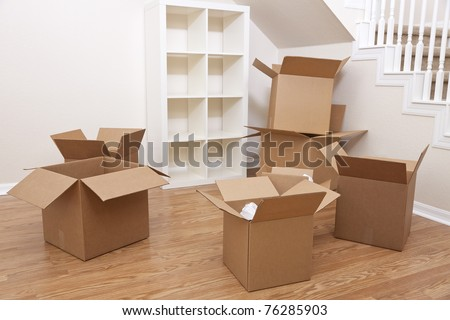 Empty room full of cardboard boxes for moving into a new home. - stock photo