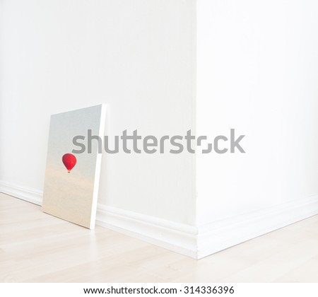 Empty room interior with artwork picture frame standing on wooden floor. Bright white scandinavian design and clean contemporary architecture. The room works as backdrop for a new office or gallery. - stock photo