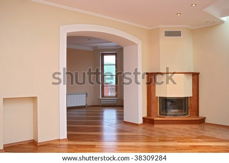 Empty room with a parquet floor, a portal in the next room, a fireplace and a window