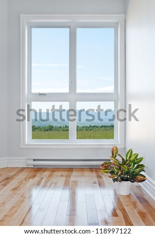Empty room with beautiful view over field and mountains. - stock photo