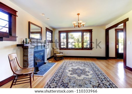 Empty room with fireplace, chairs and rug in an old nice house. - stock photo