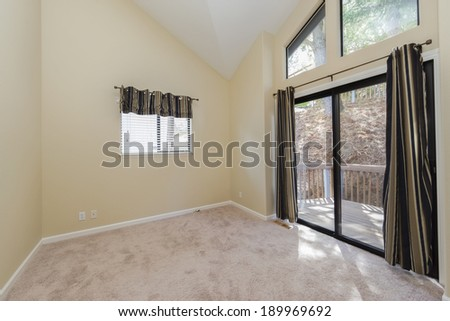 Empty room with sliding doors and balcony surrounded by nature - stock photo