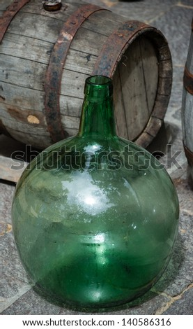 Empty round  wine bottle and wine barrel at background.  Black and white. - stock photo