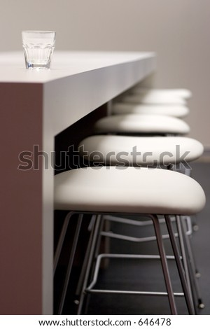 Empty row of steel chairs at a bar and glass