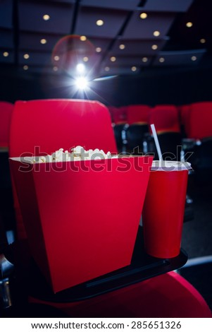 Empty rows of red seats with pop corn and drink at the cinema - stock photo