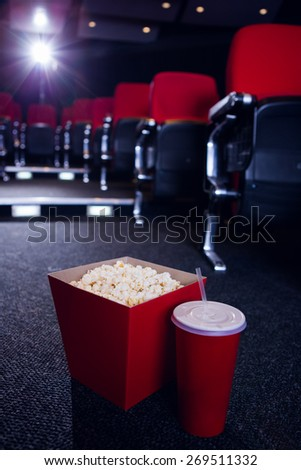 Empty rows of red seats with pop corn and drink on the floor at the cinema - stock photo